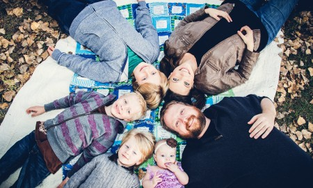 Amy Green with her husband and their four living children, on a favorite blanket that belonged to Joel, their son who died from a brain tumor.